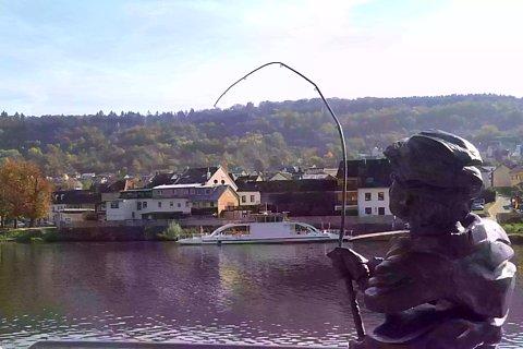 Anglerstatue aus Messing, die auf die gegenüberliegende Flussseite blickt, im Hintergrund eine Fähre