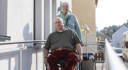 Mann im Rollstuhl auf einer Rampe im Eingansbereich eines Gästehauses, dahinter eine ältere Frau, die einen Koffer hinter sich herzieht