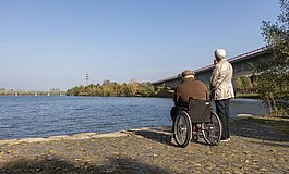 Mann im Rollstuhl mit älterem Pärchen am Flussufer mit Blick auf den Zusammenfluss von Saar und Mosel