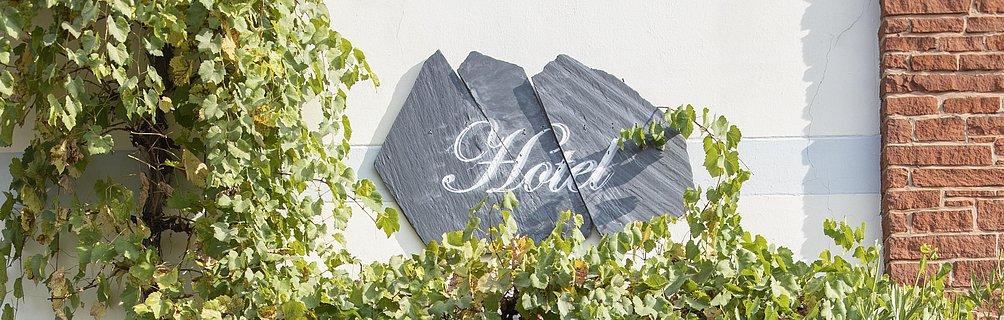 """""""Hotel""""-Schild auf Schiefertafeln an der Außenfassade eines Hotels, umrankt von Wildem Wein"""