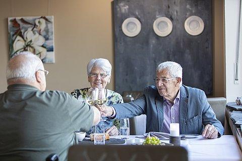 Ein älteres Ehepaar und ein Mann im Rohlstuhl stoßen mit Weingläsern an