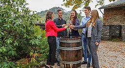 Gruppe junger Menschen um ein Weinfass stehend, beim Anstoßen