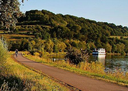 Zwei Radfahrer auf dem Radweg bei Ockfen, im Hintergrund ein Schiff auf der Saar