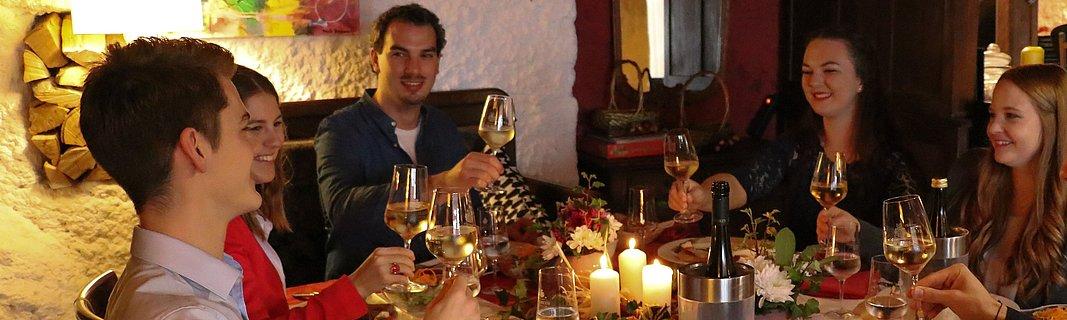 Gruppe junger Menschen beim Anstoßen an reich gedecktem Tisch im Kerzenlicht