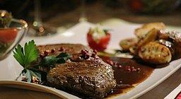 Saftiges Stück Fleisch in Soße mit Beilage