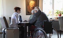 Mann im Rollstuhl mit älterem Pärchen und Hoteldame an einem Tisch im Hotel, im Vordergrund ein Koffer