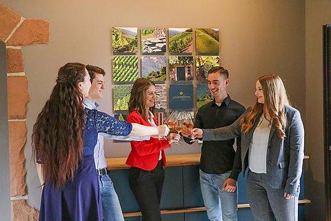 Gruppe junger Menschen beim Anstoßen in einer Vinothek