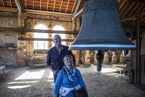 Eine Frau im Rollstuhl mit ihrem Partner unter einer Glocke im Glockengießerei-Museum in Saarburg