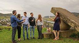 Gruppe junger Menschen beim Anstoßen neben einer Steinskulptur, Blick auf das Moseltal