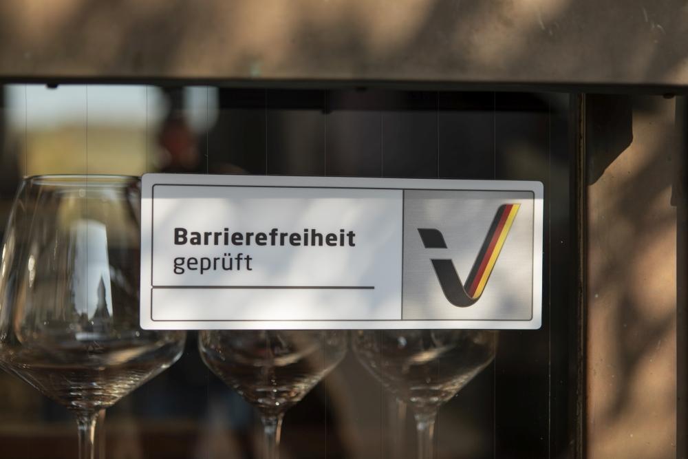 """Aufkleber """"Barrierefreiheit geprüft"""" an der Fensterscheibe eines Hotels, im Hintergrund Weingläser"""